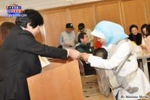 Madre indonesiana recibiendo su certificado acompañada de su bebé.